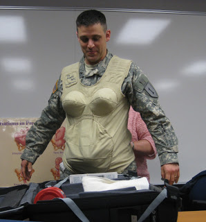 Pregnant-and-girl simulator, forced on American troops by feminists. The intention obviously is to humiliate, and they have succeeded. The problem is, first, that we have troops willing to put up with this and second, and far worse, is that the generals, who know perfectly well the effects of this sort of thing, have let the military become the playground of feminists, homosexuals, transvestites, transgenders, single mothers, and so on. They value their careers over the military.