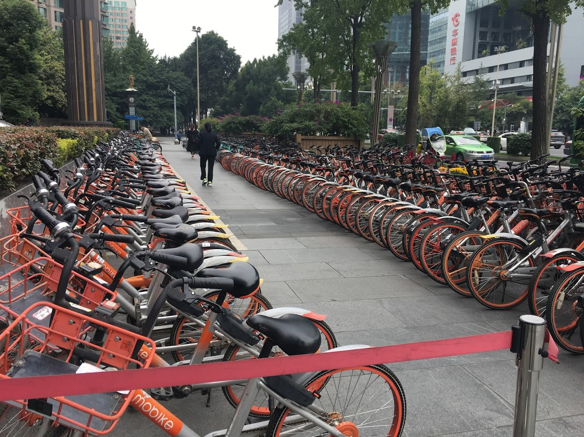 Bicycle deposits like this one are everywhere. Each ride has an electronic gizz which that lets you rent it using–what else?–WeChat. The system is not robustly communistlc: Different companies paint their bikes in different colors, and have sales to compete. Phredfoto.