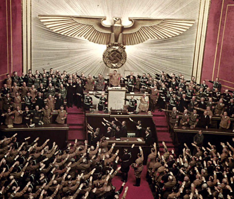 Hitler is saluted at this special session of the German Reichstag on April 28, 1939. On this occasion, the Chancellor delivered a widely anticipated address in response to a much-publicized challenge by American president Franklin Roosevelt. Millions around the world listened on radio to Hitler's two hour speech as he delivered it. In the US, all three major radio networks broadcast it live, with running English-language translation. The next day, it was the leading news item on the front page of every major American daily newspaper.